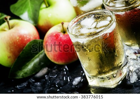Cold apple juice with crushed ice, fresh apples with green leaves on a dark background, selective focus - stock photo