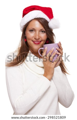 Cold attractive young woman with a cute smile in a festive red Santa hat sipping a hot mug of coffee that she is cradling in her hands to warm up in the winter weather, on white - stock photo
