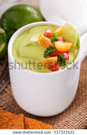 Cold avocado soup with tomato and herb salsa and tortilla chips
