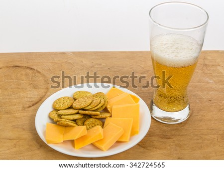 Cold beer and extra sharp cheddar cheese with crackers on rustic wooden counter with white background and copy space. - stock photo