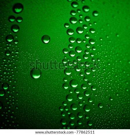 cold beer background. Misted glass of classic green bottle, macro shot. - stock photo