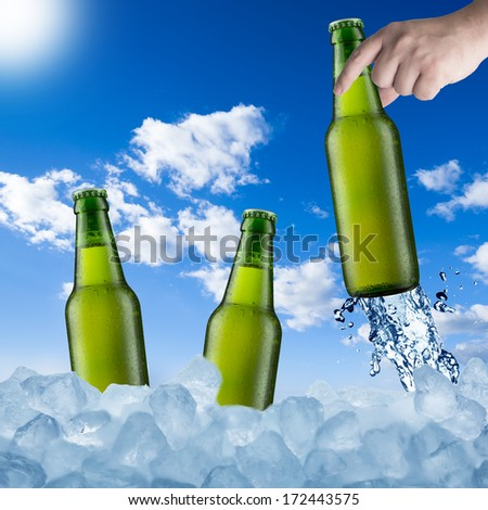 Cold Beer Bottle in Ice Cubes in Hot Summer Day - stock photo