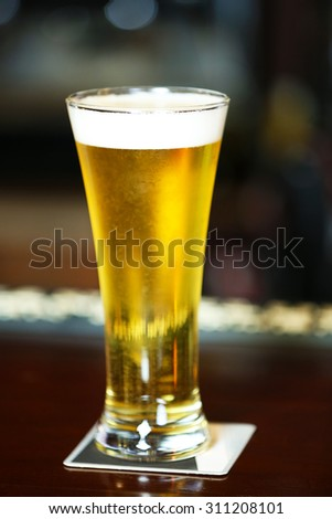 Cold beer glass on bar or pub desk - stock photo