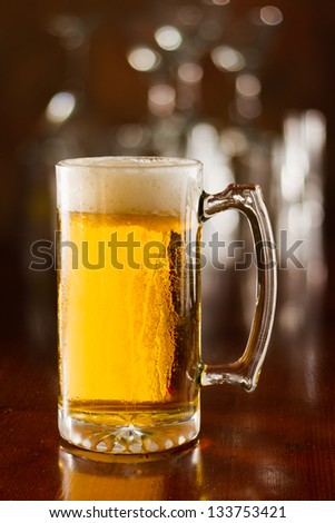 cold beer in a chilled mug served on a busy bar top - stock photo