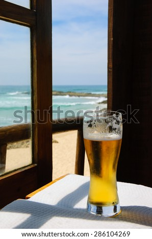 Cold beer on cafe terrace with the view on the ocean beach through the opened window. Algarve, Portugal. A game of light an shadow. - stock photo