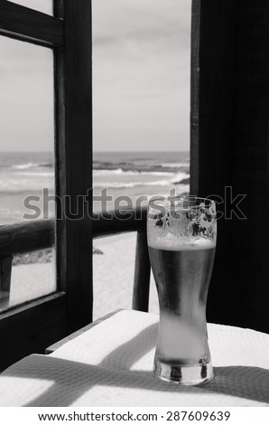 Cold beer on cafe terrace with the view on the ocean beach through the opened window. Algarve, Portugal. A game of light an shadow. Aged photo. Black and white. - stock photo