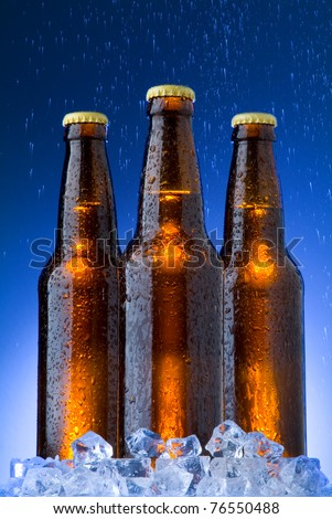 Cold Beer On Ice and Rain on Blue Background