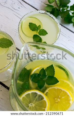 Cold beverage with lemon, lime and mint - stock photo