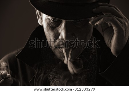Cold blooded assassin adjusting his hat with cigarette smoke came out of his mouth, in sepia color style - stock photo
