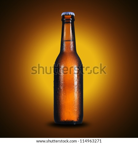 Cold bottle of light beer on yellow background - stock photo