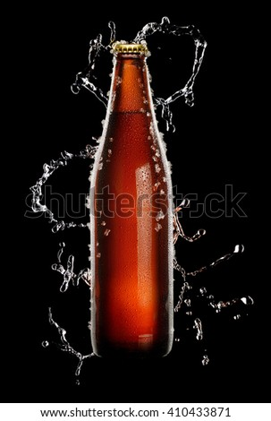Cold brown bottle of beer with water droplets and ice over black background in splash of water - stock photo