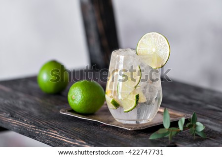 Cold cocktail with lime, lemon, tonic, vodka and ice on vintage background - stock photo