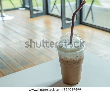 Cold coffee in plastic cup on a wooden table at cafe. Cup of cappuccino coffee - stock photo