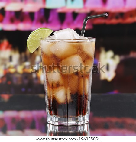 Cold cola drink or Cuba Libre Cocktail with ice cubes in a bar or a party - stock photo