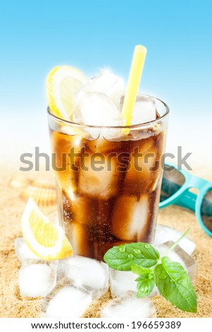 Cold cola or ice tea in a tall glass with lemon, mint leaves on sand background - beach bar summer holiday cold beverages menu. Layout with free text space. - stock photo