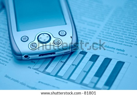 Cold cyan blue toned handheld computer and financial magazine chart. - stock photo
