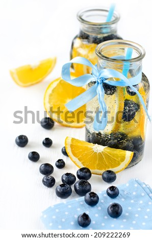 Cold drink in glasses with straws and berries - stock photo