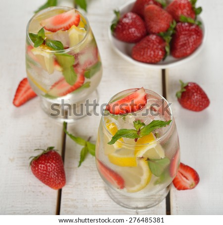 Cold drink with strawberries, lemon and mint on a white background - stock photo