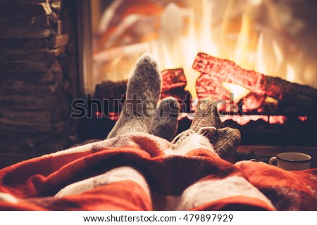 Cold fall or winter evening. People resting by the fire with blanket and tea. Closeup photo of feet in woolen socks. Cozy scene.