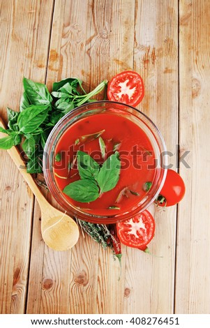 cold fresh diet tomato soup with basil thyme and raw tomatoes in transparent bowl over red mat on wood table ready to eat - stock photo