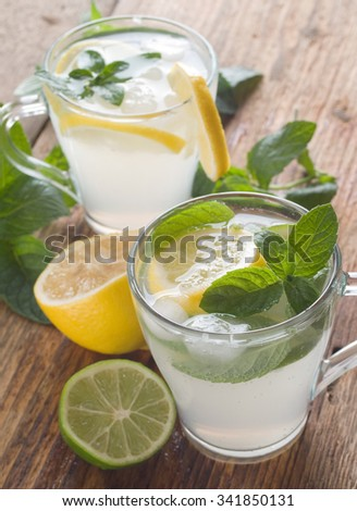 Cold fresh lemonade drink on a wooden background