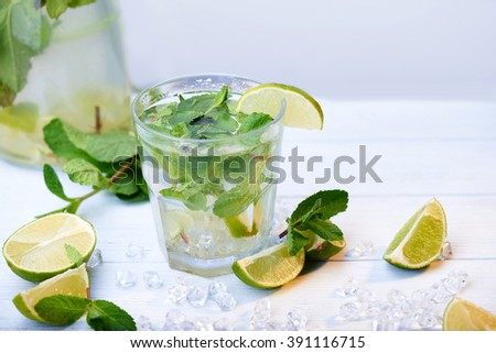 Cold fresh lemonade drink with slice of lime on the glass. Slices of lime and mint leaves on a  white wooden background