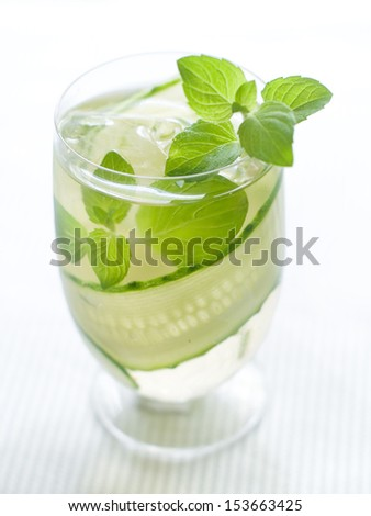 Cold fresh lemonade with cucumber and ice, selective focus