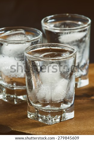 Cold fresh water with ice in a glass on a dark background in vintage style, selective focus - stock photo