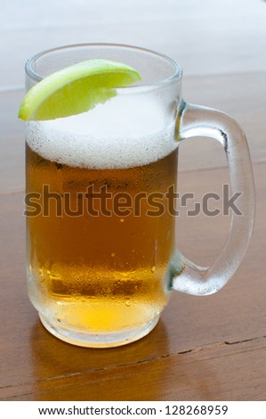 Cold glass of beer with a lime - stock photo