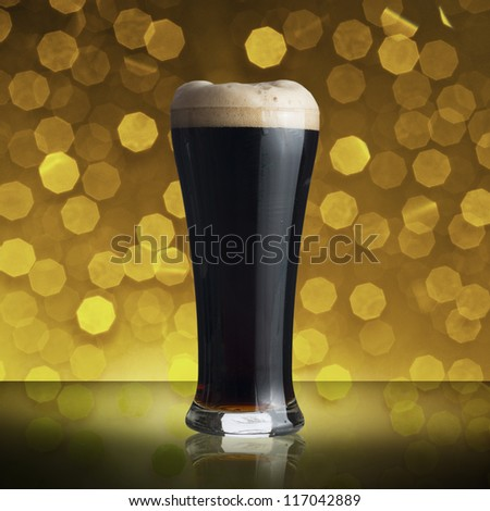Cold glass of dark beer on yellow bokeh background - stock photo
