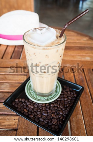 Cold glass of milk espresso and heart ice cube