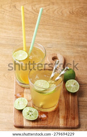 cold gold soft drink from lime and honey with gold straw on wooden board