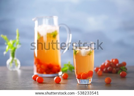 Cold grape cocktail and fresh berries on blurred background