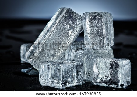 Cold group of ice cubes on a wet black surface - stock photo