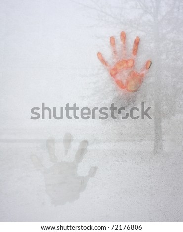 Cold Hand on Icy Window - stock photo