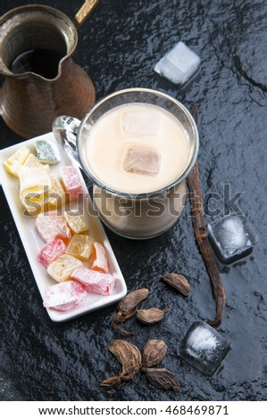 Cold ice coffee with milk in glass cup and copper cezve, spices and sweets on black stone background, top view