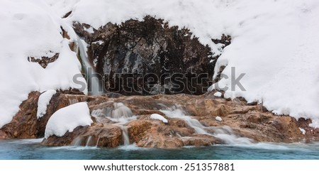 cold icy waterfall between rocks in winter snow - stock photo