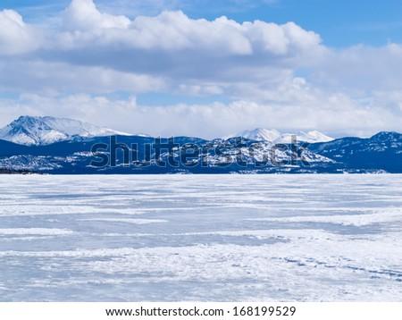 Cold icy winter landscape of frozen Lake Laberge, Yukon Territory, Canada - stock photo