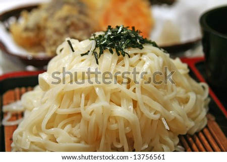 Cold japanese udon noodles on a bamboo mat with sprinkles of seaweed - stock photo