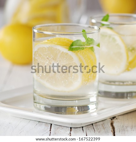 Cold lemon water with ice and mint, selective focus and square image - stock photo