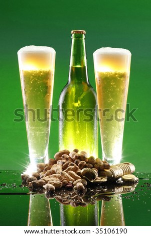 Cold malt liquor and bottle, roasted peanuts, opener and cap - stock photo