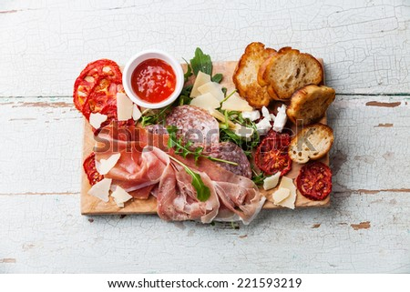 Cold meat plate and bread on wooden background  - stock photo