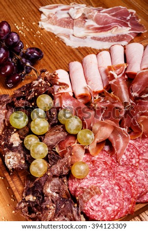 Cold meat plate, slices prosciutto, ham,beef jerky,sausage, salami with grapes and spice on wooden cutting board - stock photo