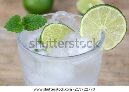 Cold mineral water drink with ice cubes and lime - stock photo