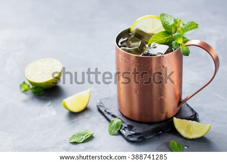 Cold Moscow Mules cocktail with ginger beer, vodka, lime Grey stone background - stock photo