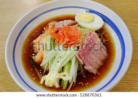 Cold noodles with egg, pork, ham, salad dressing, carrot, cucumber, shrimp. It's Japanese food on the wood table and it's has smell good enough to eat. Look tasty and also delicious.