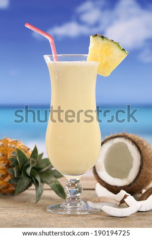 Cold Pina Colada cocktail with fruits on the beach while on vacation - stock photo