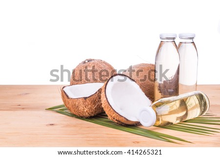 Cold pressed extra virgin coconut oil in bottles with coconut fruits as background