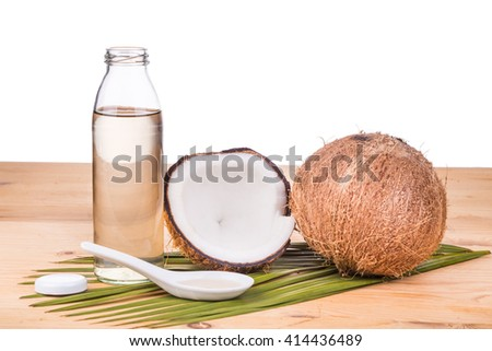 Cold pressed extra virgin coconut oil in one bottle with coconut fruits as background