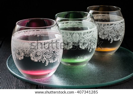 Cold pure mineral water in beautiful glasses with ornaments on the dark background  - stock photo